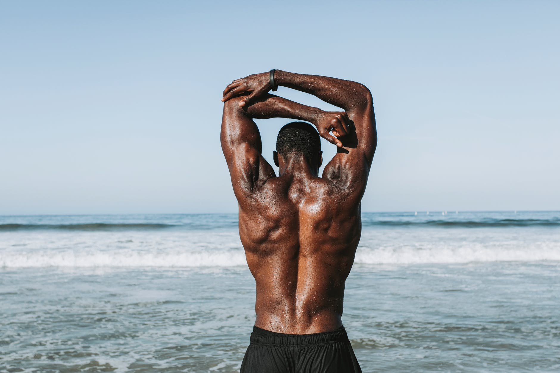 man stretching arms in front of ocean