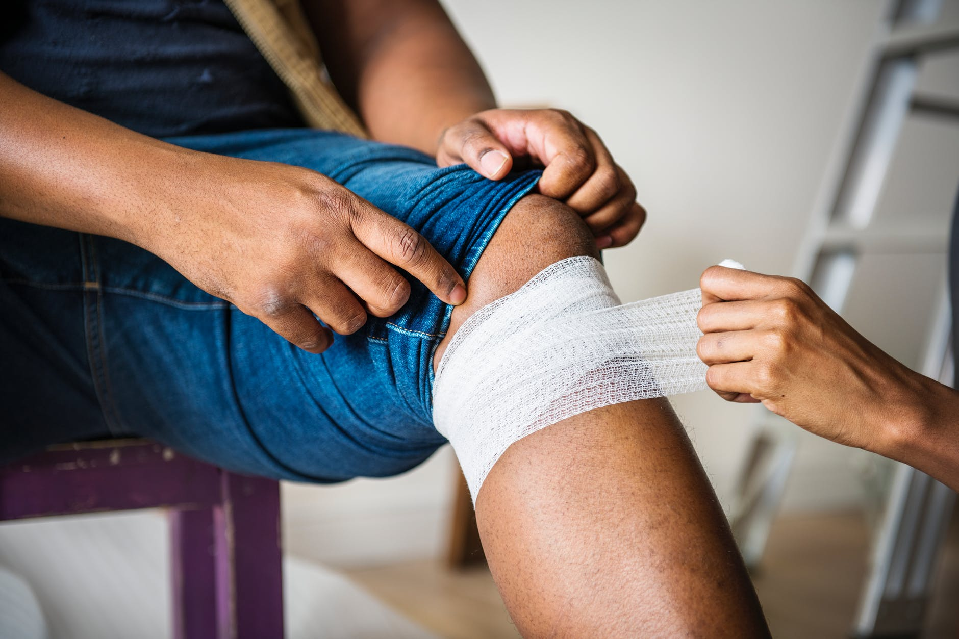 person putting bandages on another person s knee
